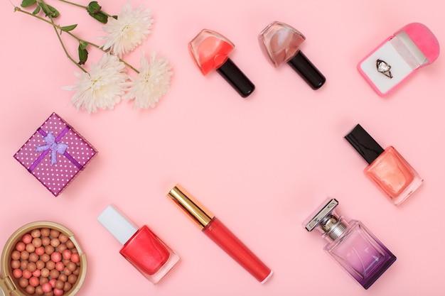 Geschenkboxen, pulver, nagellack, parfümflaschen, lippenstift, pinsel und blumen auf rosafarbenem hintergrund. accessoires für damen. ansicht von oben.