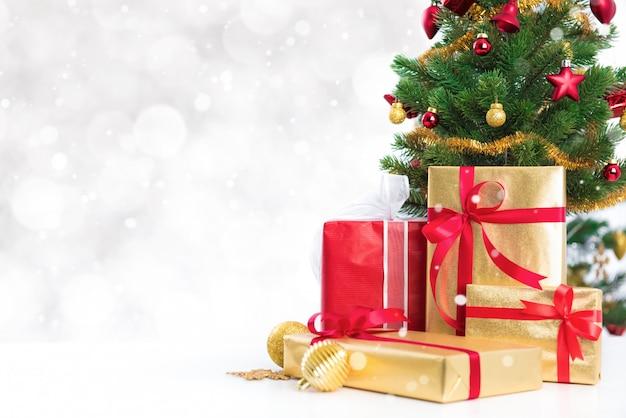 Geschenkboxen und bunter verzierter weihnachtsbaum auf weißem bokeh hintergrund