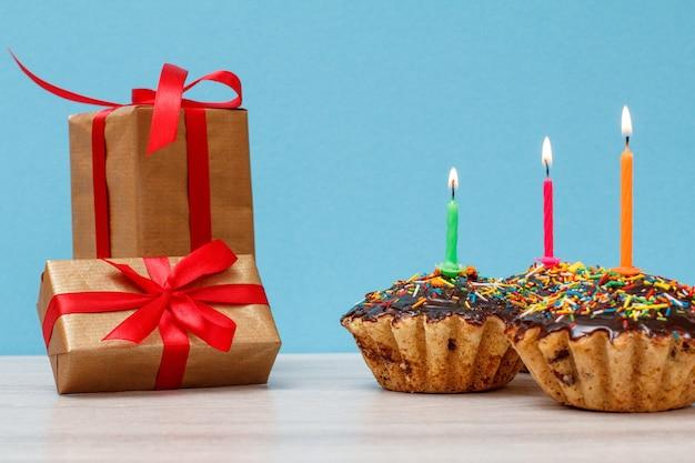 Geschenkboxen und drei leckere geburtstags-cupcakes mit schokoladenglasur und karamell, dekoriert mit brennenden festlichen kerzen auf blauem hintergrund. alles gute zum geburtstag minimales konzept.