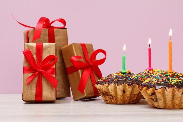 Geschenkboxen und drei leckere geburtstags-cupcakes mit schokoladenglasur und karamell, dekoriert mit brennenden festlichen kerzen auf rosafarbenem hintergrund. alles gute zum geburtstag minimales konzept.