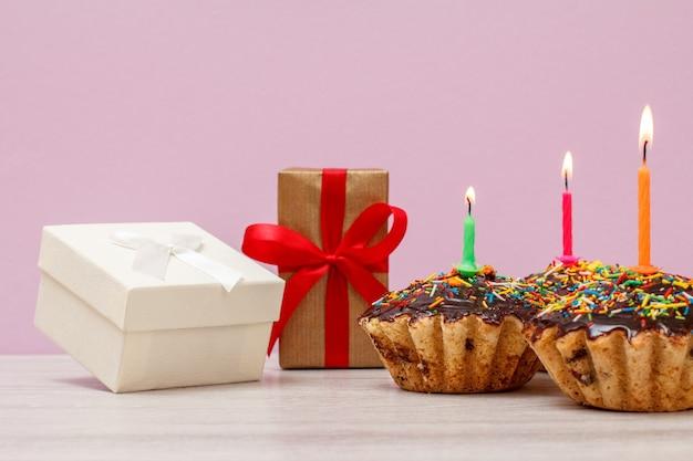 Geschenkboxen und drei leckere geburtstagsmuffins mit schokoladenglasur und karamell, dekoriert mit brennenden festlichen kerzen auf rosafarbenem hintergrund. alles gute zum geburtstag minimales konzept.