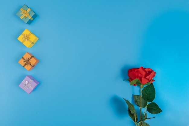 Geschenkboxen und eine rote rose auf blauem hintergrund