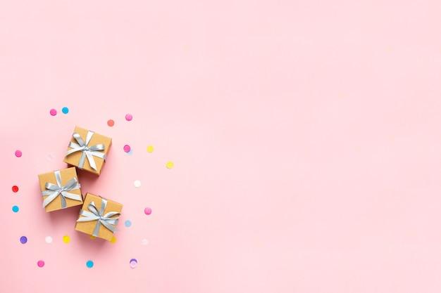 Geschenkboxen und farbkonfetti auf rosa tisch