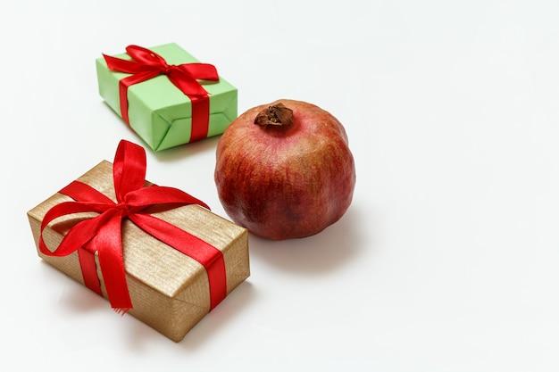 Geschenkboxen und reife granatapfelfrucht auf dem weißen hintergrund... ansicht von oben.