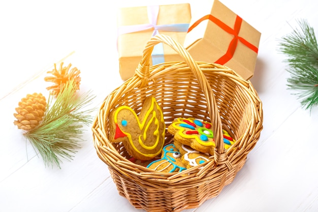 Geschenkboxen und selbst gemachte gemalte lebkuchenplätzchen unter tannenzweigen und geschenken auf weißem hintergrund. süßes geschenkkonzept des weihnachten und des neuen jahres. lustige süße lebensmittelnahaufnahme. kopieren sie platz für text