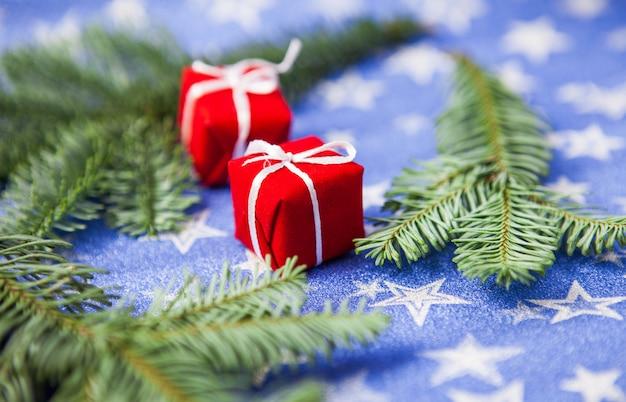 Geschenkboxen und tannenzweige auf hintergrund des blauen sternes, konzept der feier des neuen jahres