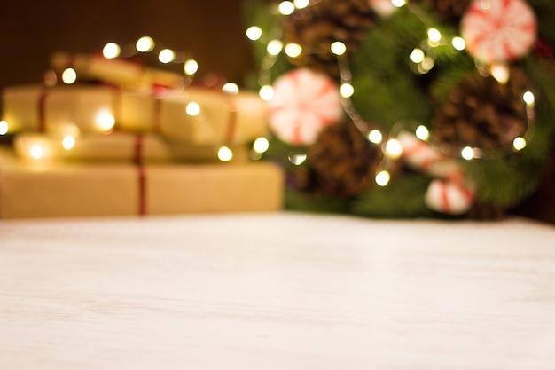 Geschenkboxen und weihnachtskranz mit leuchtender girlande. unscharfer hintergrund ohne fokus mit bokeh