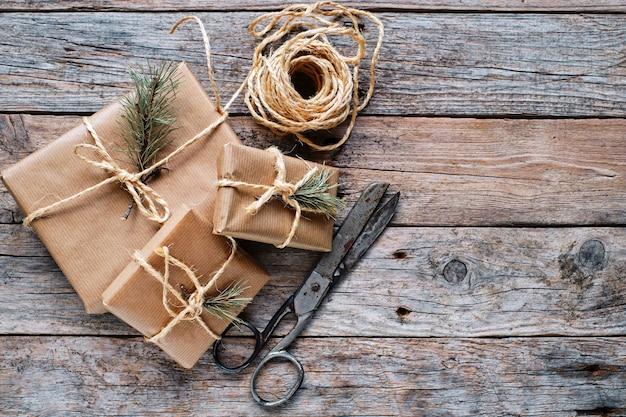 Geschenkboxen verpackt in kraftpapier mit jutebogen auf rustikalem holzhintergrund mit kopierraum. ansicht von oben.
