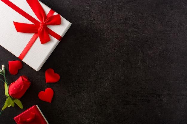 Geschenkboxen verziert mit roten herzen und rotrose