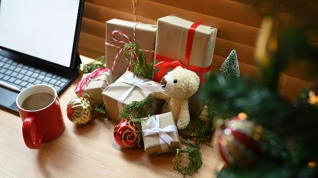 Geschenkboxen, weihnachtsschmuck und teddybärdekorationen auf holztisch.