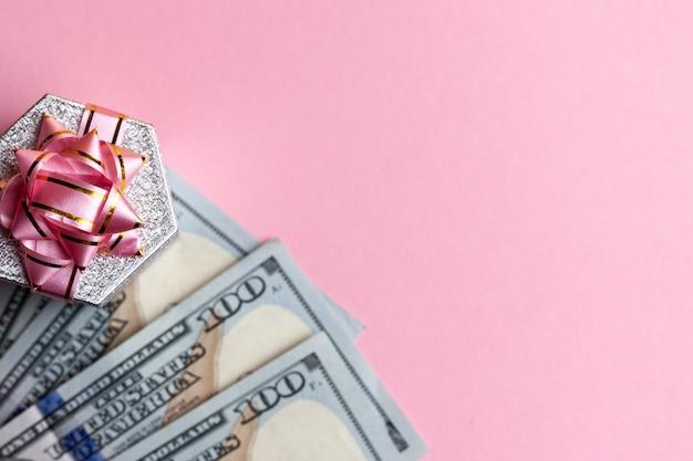 Geschenkboxstand auf bargelddollar am rosa hintergrund. draufsicht kopieren sie platz für design.