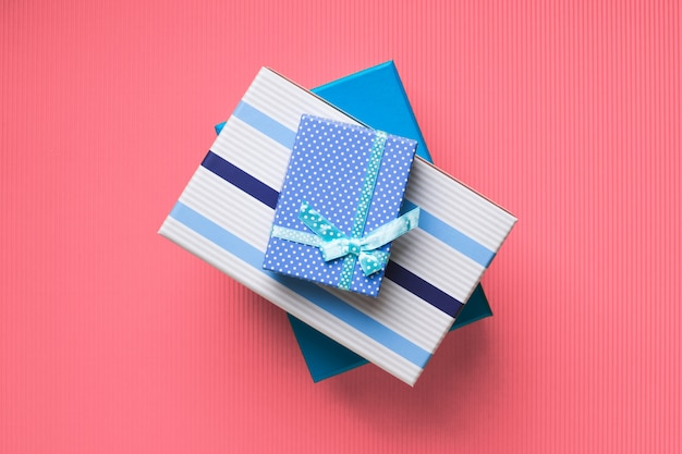 Geschenkboxstapel auf rosa koralle