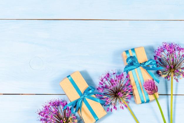 Geschenke auf einem blauen hölzernen hintergrund mit lila blumen.