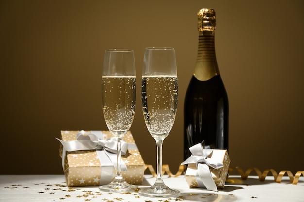 Geschenke, champagnergläser und flasche auf goldenem raum, platz für text
