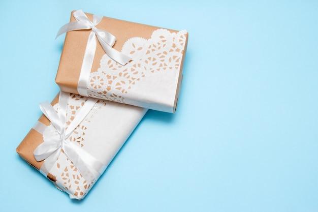 Geschenke des kraftpapiers auf einem blauen hintergrund mit kopienraum.