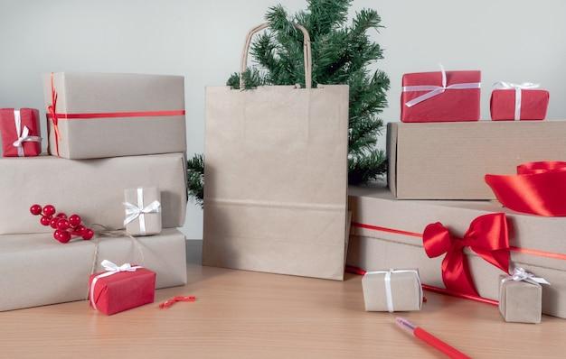 Geschenke, einkaufstasche, weihnachtsbaum und verpackungsboxen auf dem tisch, lieferkonzept.
