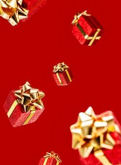 Geschenke fliegen in die Luft auf einem roten Hintergrund. Verkauf. Schwebekonzept. Weihnachtsplan.
