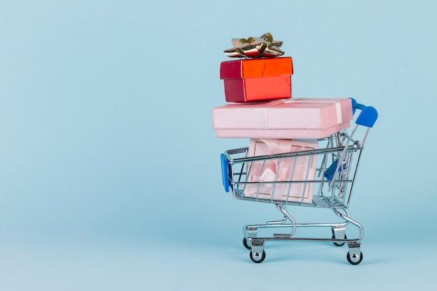 Geschenke gestapelt in der einkaufskarte auf blauer oberfläche