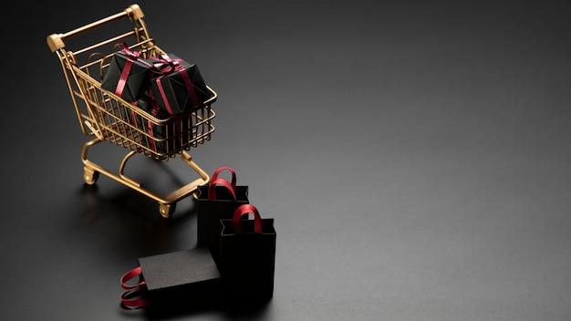Geschenke im goldenen einkaufswagen mit kopienraum