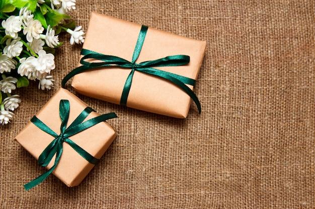 Geschenke im kraftpapier mit den weißen blumen, die auf sackleinen legen.