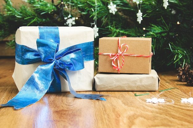 Geschenke in bastelpapier auf dem hintergrund des weihnachtsbaumes. ein weihnachtsgeschenk. winterkomposition. weiße schneeflocken. neujahr. geschenke hautnah