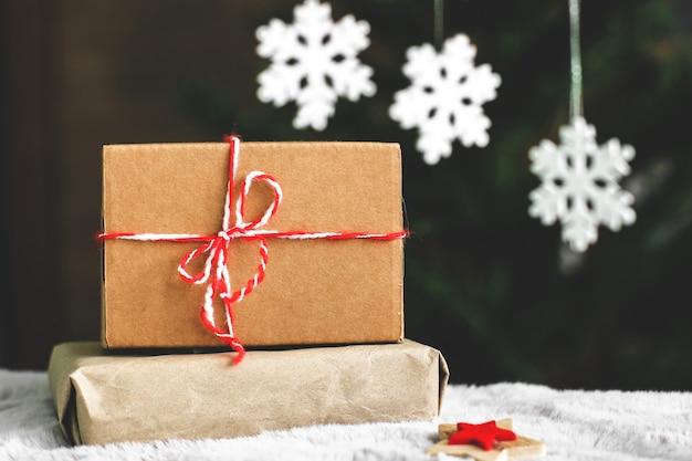 Geschenke in bastelpapier. ein weihnachtsgeschenk. winterkomposition. weiße schneeflocken. geschenk nahaufnahme