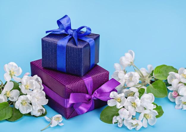 Geschenke in blauem und lila papier, weiße blüten des apfelbaums. blauer hintergrund, kopierraum.