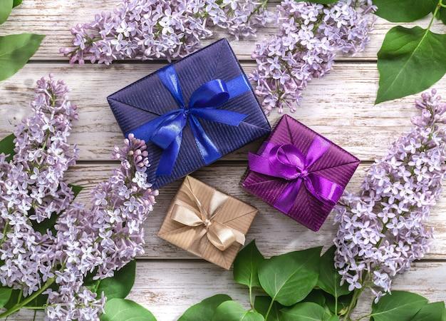 Geschenke in blauem und violettem papier, zweige und blätter von lila blüten.
