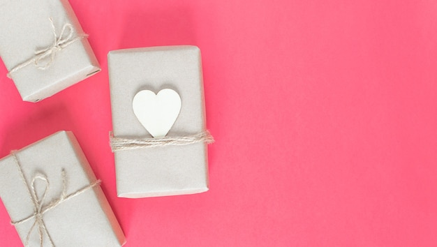 Geschenke in umweltfreundlichen bastelverpackungen für den urlaub auf einem rosa hintergrund.