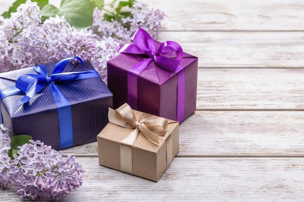 Geschenke in weihnachtsboxen mit bändern und schleifen. zweige von blüten von flieder.