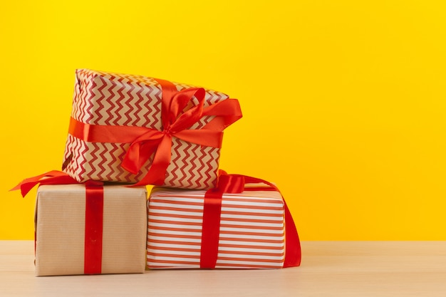 Geschenke mit bändern auf hellem gelbem hintergrund