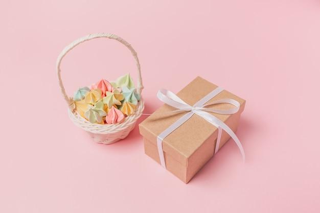 Geschenke mit süßigkeiten auf lokalisierter rosa oberfläche, liebes- und valentinsgrußkonzept