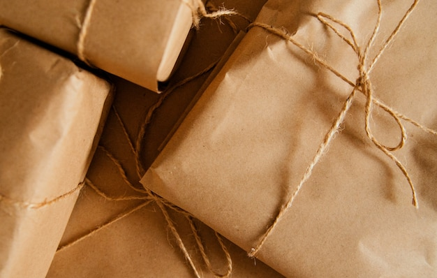 Geschenke oder postpaket in kraftpapier verpackt. schachteln in verschiedenen größen mit bindfäden gebunden.