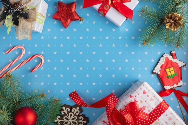 Geschenke, tannenbaumaste mit tannenzapfen, schneeflockenlebkuchen, hauslebkuchen, süßigkeiten und flitter auf blauem hintergrund mit muster von sternen weihnachten, winter, konzept des neuen jahres. ansicht von oben