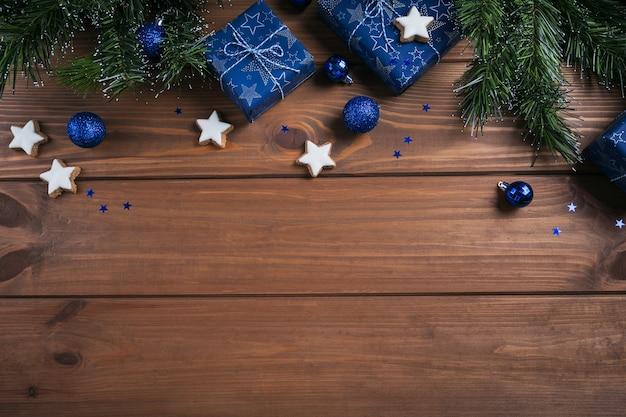 Geschenke, tannenzweige, blaue verzierungen auf holz