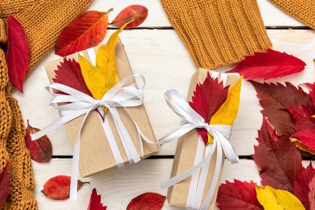 Geschenke umgeben von kürbissen und herbstlaub