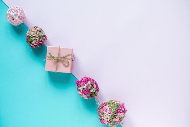 Geschenke und blumen auf pastellblauem und rosa tisch