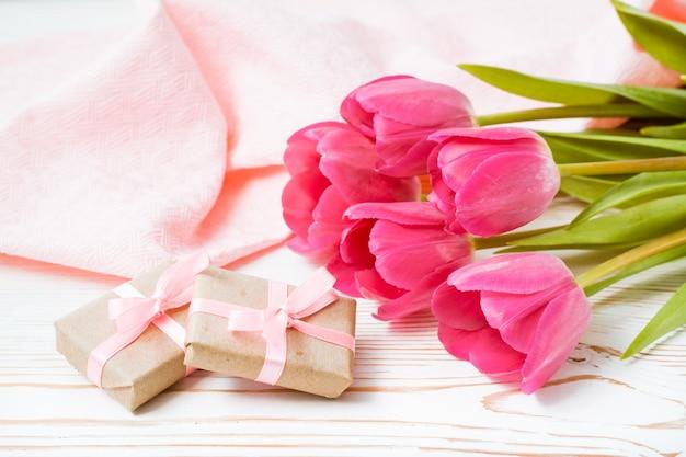 Geschenke und blumenstrauß von rosa tulpen auf dem tisch
