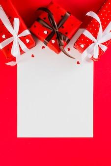 Geschenke und herzen über leerem papier