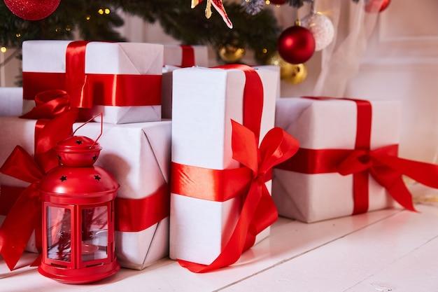 Geschenke unter der roten schleife des weißen papierweihnachtsbaums.