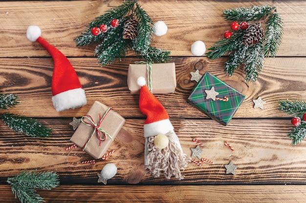 Geschenke, weihnachtsmann, tannenzweige und beeren, auf einem hölzernen beschaffenheitshintergrund. von oben betrachten. handarbeit.