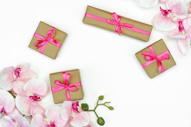 Geschenkgeschenkboxen mit orchideenblumen auf weißem hintergrund
