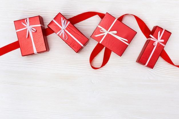 Geschenkkästen rot gefärbt auf weißem hölzernem hintergrund. kopieren sie platz.