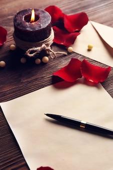 Geschenkkarte zum valentinstag mit stift, roten blütenblättern und kerze auf holzoberfläche