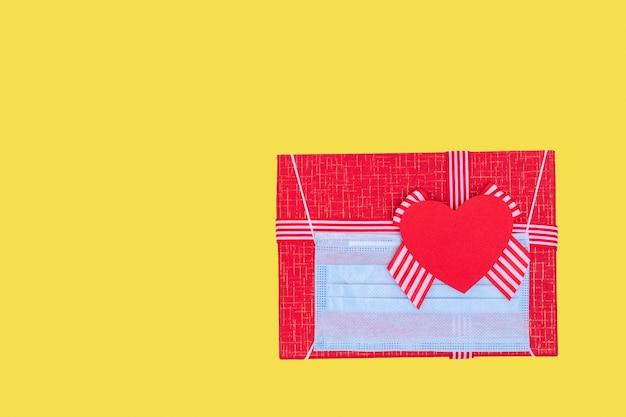 Geschenkkonzept während der coronavirus-pandemie. rote geschenkbox mit dem tragen einer medizinischen schutzmaske und des liebesherzens des roten papiers auf dem trendigen beleuchtenden gelben 2021 hintergrund, kopienraum