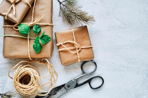 Geschenkpakete verpackt in kraftpapier, gebunden mit jute, schere und schnur auf weißem strukturiertem untergrund. ansicht von oben.