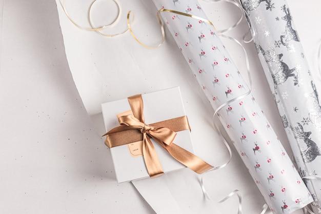 Geschenkpapier. festliches geschenkpapier zu weihnachten. festliche farben in weiß, gold und silber. ferienzeit. handgemachte geschenkbox verpackung.