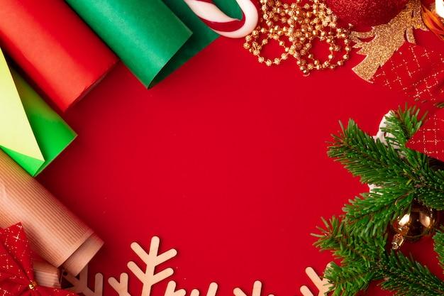 Geschenkpapier und gegenstände für weihnachten dekorieren auf rotem hintergrund