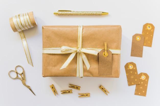 Geschenkschachtel mit etikett in der nähe von schere und farbband