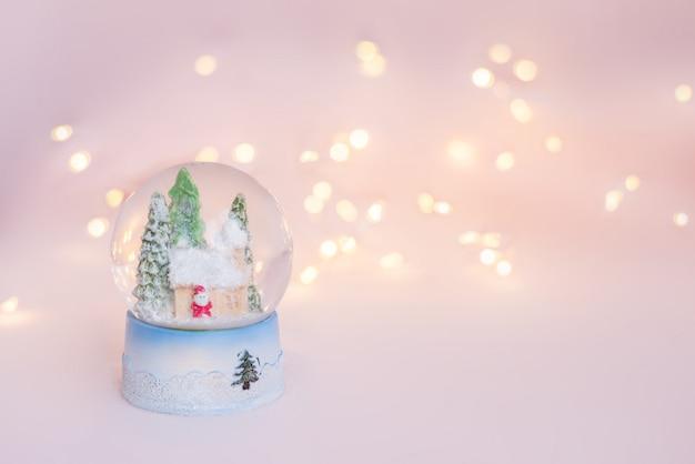 Geschenkschneekugelandenken auf einem hellrosa hintergrund mit weihnachtslichtern